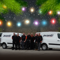Avanti workers in front of avanti branded vans, with christmas tree branches and lights